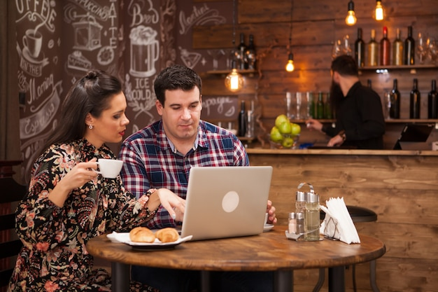 レストランでの商談会での魅力的なカップルが、ランチタイムに仕事の瞬間について話し合っています。流行に敏感なパブ。