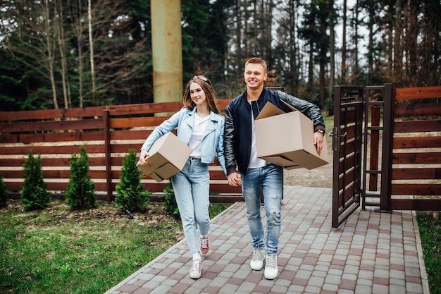 Привлекательная пара проверяет свою квартиру для сдачи в аренду на время отпуска, обнимается и счастлива провести вместе медовый месяц в отпуске.