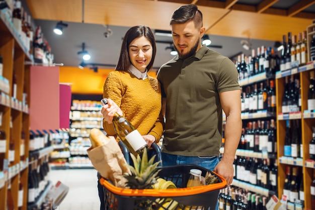 Attractive couple choosing wine in grocery supermarket