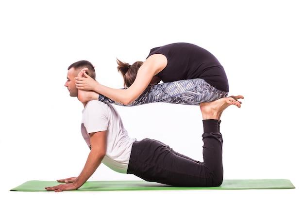 Coppie attraenti che fanno yoga insieme su priorità bassa bianca