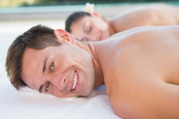 뜨거운 돌 마사지 수영장을 즐기는 매력적인 커플