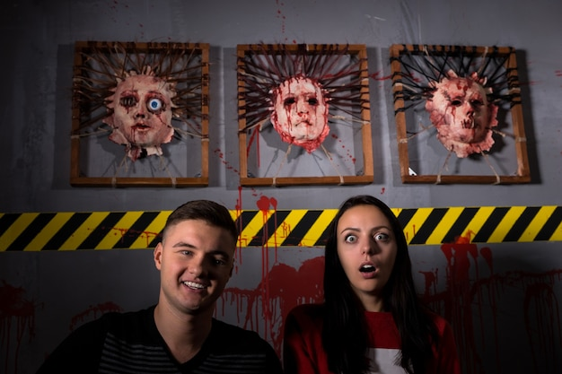 Attractive couple in front of skinned faces for scary halloween theme terror crime scene