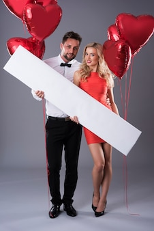 Attractive couple holding an empty placard