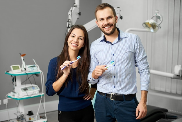 Attractive couple is standing in the dental office  of equipment and holding toothbrushes with paste. young people have a snow-white smile and look at the camera