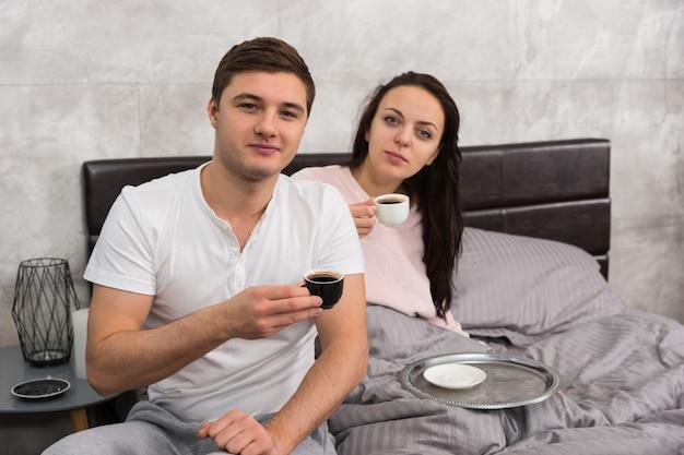 魅力的なカップルは、パジャマを着て、コーヒーを飲みながらベッドで朝食をとりながら、目が覚めたばかりです。