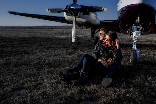Attractive couple in love is hugging each other and sitting on the ground near the helicopter on a sunny day