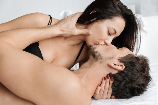 Attractive couple man and woman hugging together, while lying in bed at home or hotel apartment