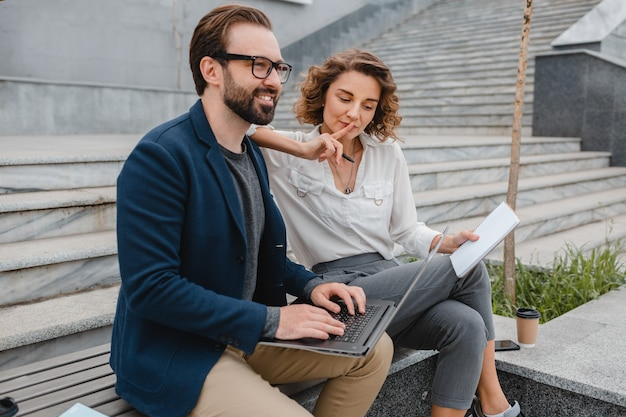 Coppia attraente di uomo e donna seduti sulle scale nel centro urbano, lavorando insieme sul laptop, sorridendo