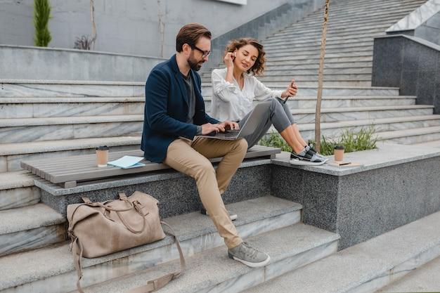 Coppia attraente di uomo e donna seduti sulle scale nel centro urbano, lavorando insieme sul laptop