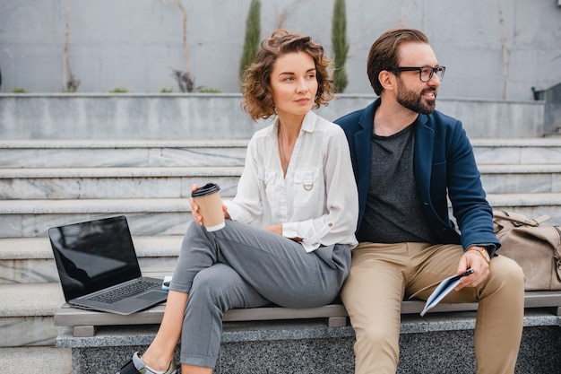 Attractive couple of man and woman sitting on stairs in urban city center