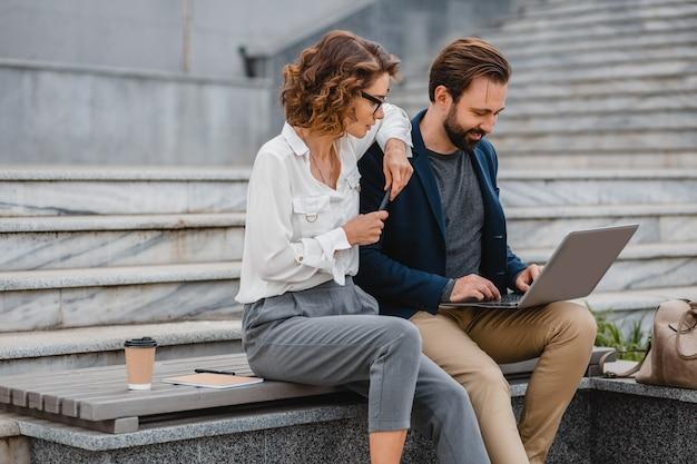 Attraente coppia di uomo e donna seduti sulle scale nel centro urbano della città