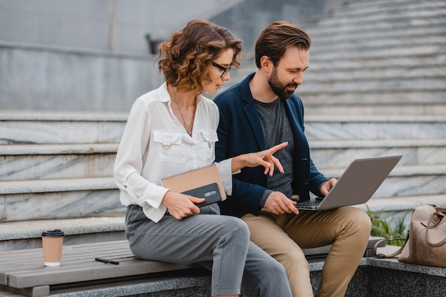 Attractive couple of man and woman talking sitting on stairs in urban city center, working together on laptop