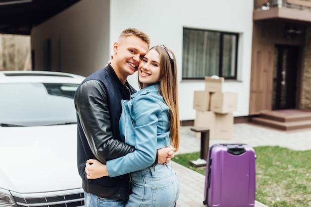 彼らの新しい白い車と家の近くの魅力的なカップル。