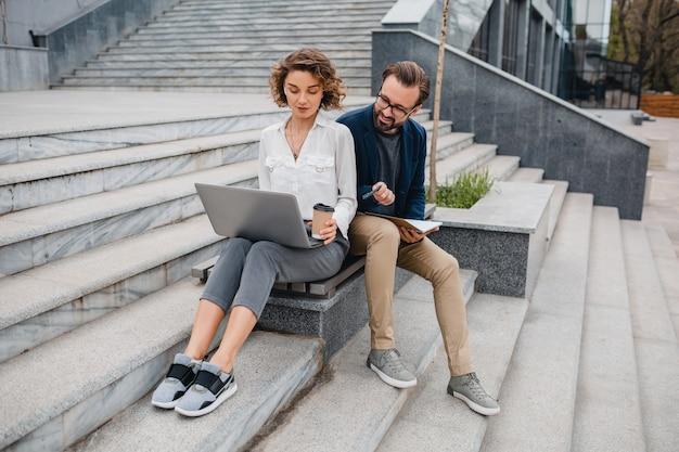 Привлекательная пара мужчина и женщина, сидя на лестнице в центре города