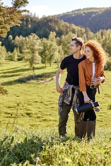 魅力的なカップルや友人は、田舎でのハイキング旅行中に、熟考しながら横を見て、周りの自然を楽しんでいます。魔法瓶で幸せな男性と赤毛の巻き毛の女性の肖像画