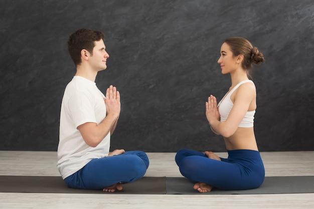 パドマサナに向かい合って座ってヨガを練習している魅力的なカップル。スポーツクラブのインテリア、コピースペースでマットの上で呼吸運動をしている蓮のポーズの若い男性と女性