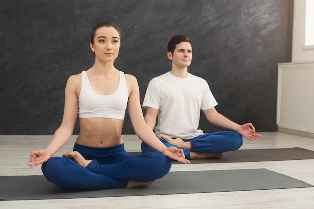 パドマサナに座ってヨガを練習している魅力的なカップル。スポーツクラブのインテリア、コピースペースでマットの上で呼吸運動をしている蓮のポーズの若い男性と女性
