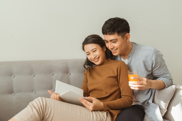 Attractive couple reading book on the sofa at home in living room