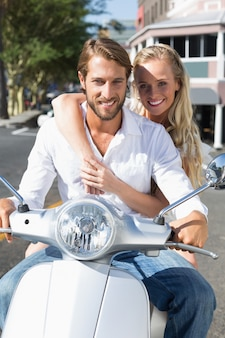 Attractive couple riding a scooter on a sunny day in the city