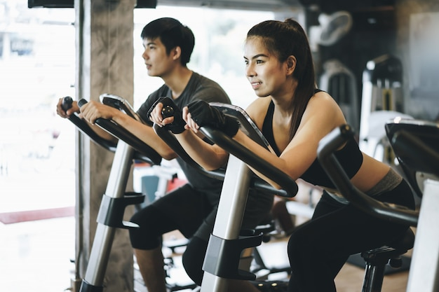 Attractive couple riding on the spinning bike at gym. working out together