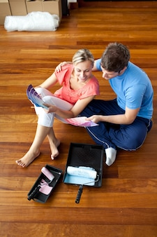 Attractive couple sits on the floor picking colors