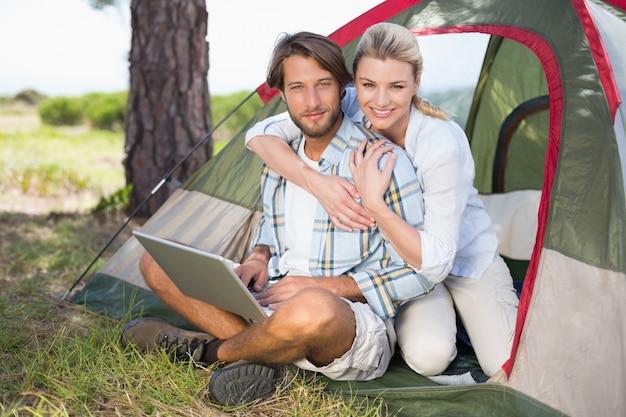 매력적인 부부는 카메라를 웃고 노트북을 사용하여 자신의 텐트 옆에 앉아