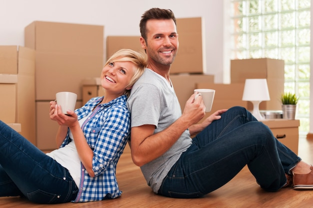 Coppie attraenti che si siedono sul pavimento a casa con le tazze di caffè