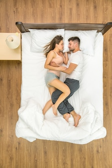 The attractive couple sleeping on the bed. view from above