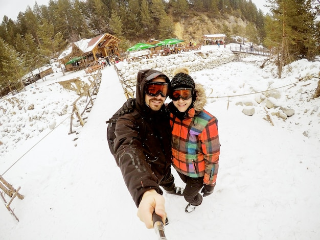 Attractive couple taking awesome selfie with a wooden cabin covered in snow