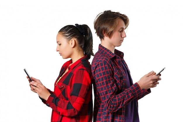 白い壁にスマートフォンを使用して魅力的なカップル