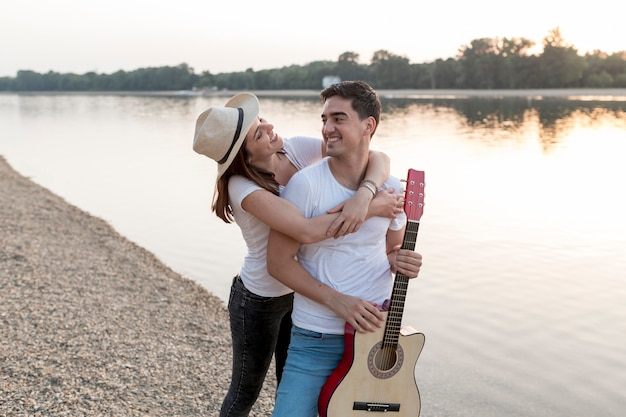 Attractive couple walking by the lake with guitar