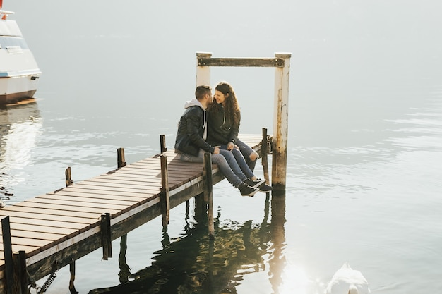Attractive couple on the wooden jetty at a lake lugano in switzerland.