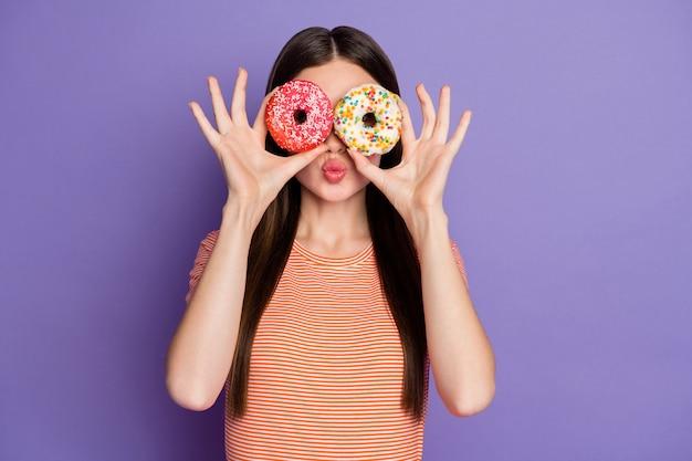 Привлекательная сумасшедшая дама держит глазированные пончики, пряча глаза, посылает воздушные поцелуи