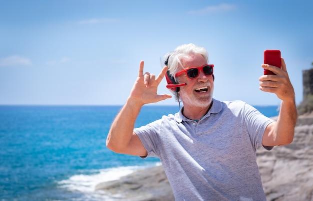 빨간 헤드폰과 선글라스를 착용하고 바다에서 셀카를 찍는 매력적인 미친 노인. 스마트폰 플레이리스트 앱으로 즐겁게 은퇴한 평온함