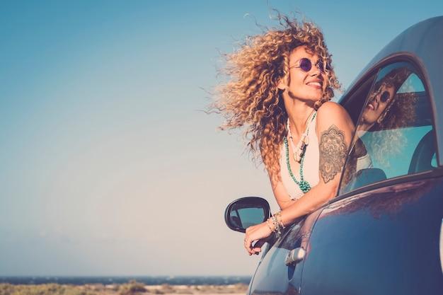 魅力的な巻き毛の金髪の若い女性は笑顔で車の外の風を楽しむ
