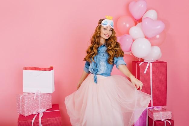 背景にプレゼントで誕生日パーティーのゲストを待っているトレンディな緑豊かなスカートダンスで魅力的な巻き毛の女の子。愛らしい若い女性は友人から受け取った風船とプレゼントを楽しんでいます