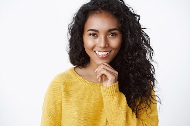노란색 스웨터를 입은 매력적인 곱슬머리 여성은 옳은 선택을 하고 생각하는 것처럼 턱을 만지고 좋은 생각을 하는 것처럼 기뻐하며 웃고 있습니다.
