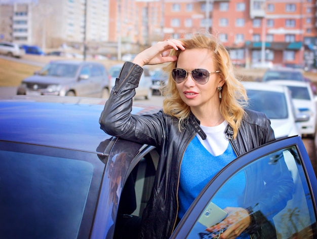 Attractive curly haired woman is standing behind her car.