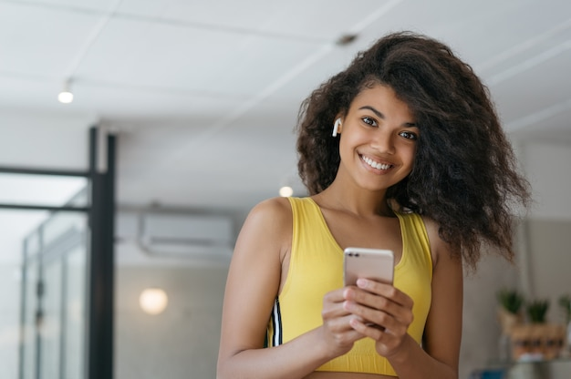 Attractive curly haired woman using smartphone with app for calorie counting