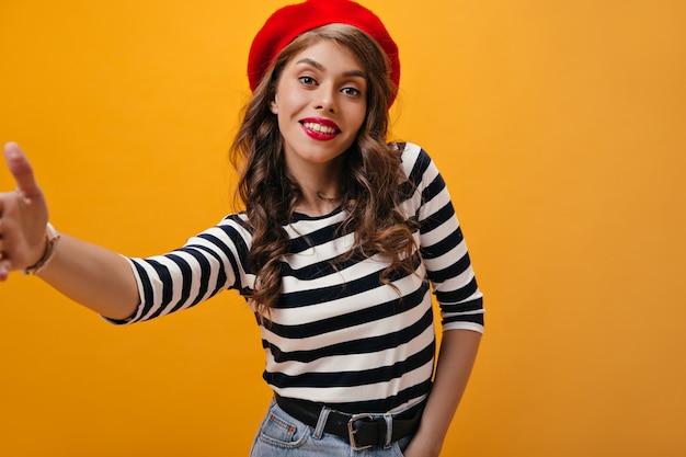 베레모에 매력적인 곱슬 여자는 오렌지 배경에 selfie를 만든다. 격리 된 배경에서 포즈 스트라이프 스웨터에 물결 모양의 머리를 가진 현대 소녀.