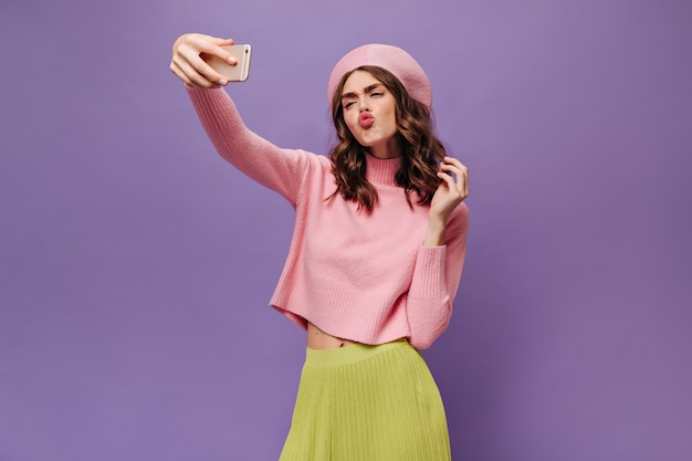緑のスカート、ピンクのベレー帽、ピンクのセーターの魅力的な巻き毛の女性は、キスを吹き、自分撮りを取り、紫色の壁に電話を保持します