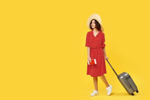 黄色の背景で旅行に行く灰色のスーツケースを引っ張る赤いドレスの魅力的な巻き毛の女性。テキスト用のスペース