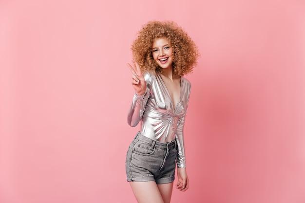 光沢のあるシルバーのトップとグレーのショートパンツの魅力的な巻き毛の女性は、ピンクのスペースにピースサインを示しています。