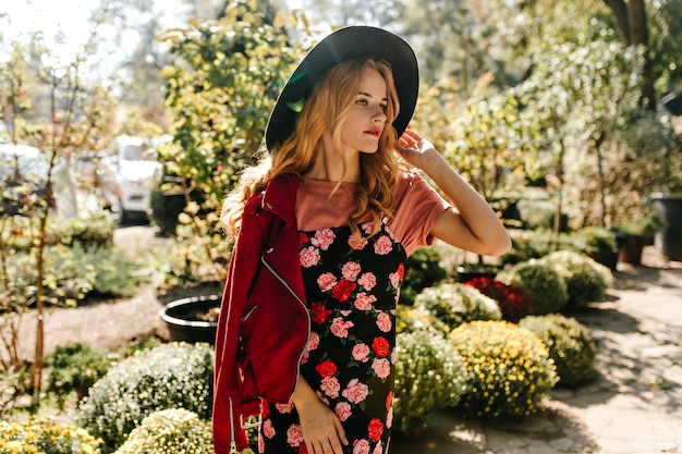 Attractive curly woman in wide-brimmed hat, red leather jacket and black dress with floral print looks thoughtfully into distance, enjoying spring day in garden.