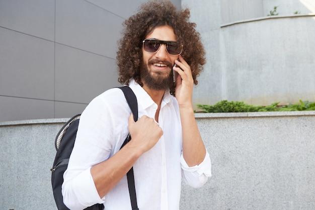 Attraente giovane maschio riccio con barba rigogliosa cammina per strada in una giornata calda, andando a fare una chiamata con il suo telefono cellulare, essendo di buon umore e sorridendo ampiamente