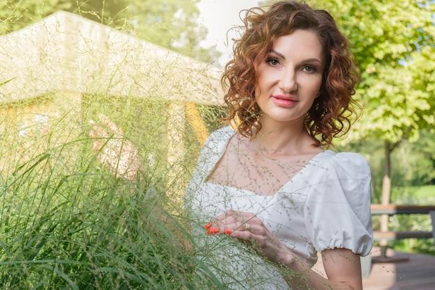 Привлекательная кудрявая женщина в белом платье рассматривает декоративные растения в своем саду