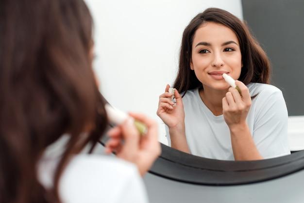 Привлекательная, милая брюнетка рисует губу губной помадой, глядя в зеркало