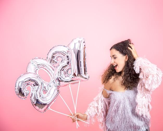 Attraente ragazza bruna carina con capelli ricci vestita a festa in posa su uno sfondo rosa con palloncini d'argento in mano per il concetto di nuovo anno