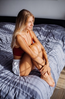Attractive cute caucasian european woman enjoys beautiful sunrise light by window, she is on bed at home