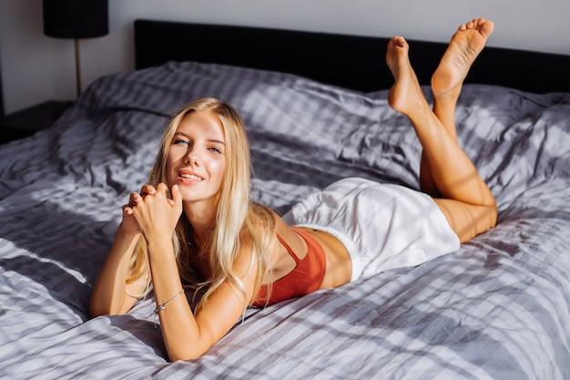 魅力的なかわいい白人のヨーロッパの女性は、窓際の美しい日の出の光を楽しんでいます、彼女は自宅のベッドにいます